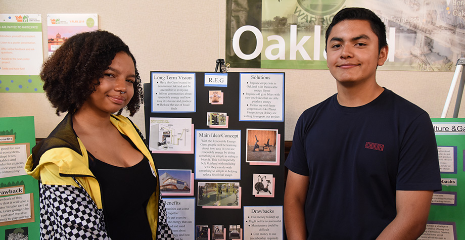 Two students standing by presentation board