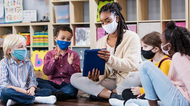 teacher and students wearing masks, sitting on floor looking at tablet