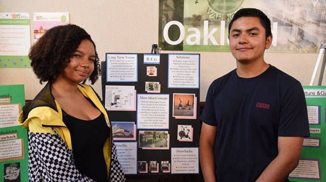 Young woman and man standing in front of a school project display