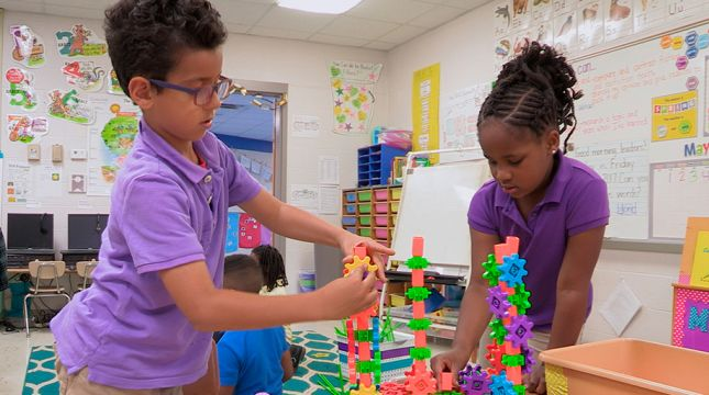 Two students work on building a structure out of colorful blocks