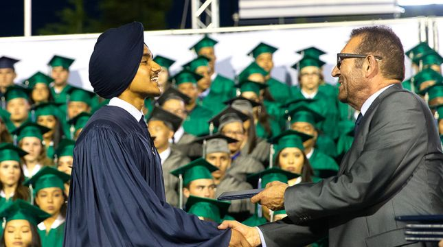 Young man in a graduation robe shaking hands