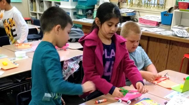 Three elementary-age children working on an arts and craft project