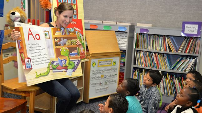 Elementary teacher reading a book to the class