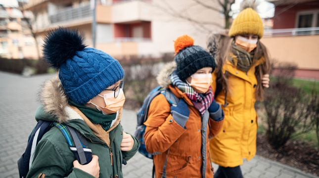 students wearing masks walking to school