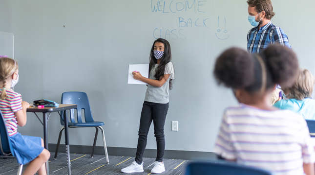 Student with mask on presenting to class
