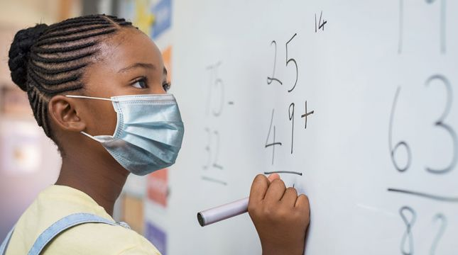 African American student wearing a mask and writing on a whiteboard.