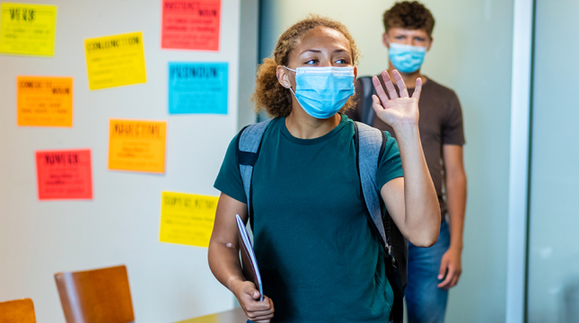 Middle school students entering a classroom wearing masks.
