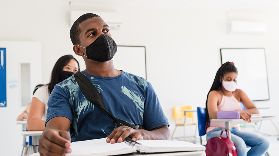 Young adults wearing masks and seated in a classroom.