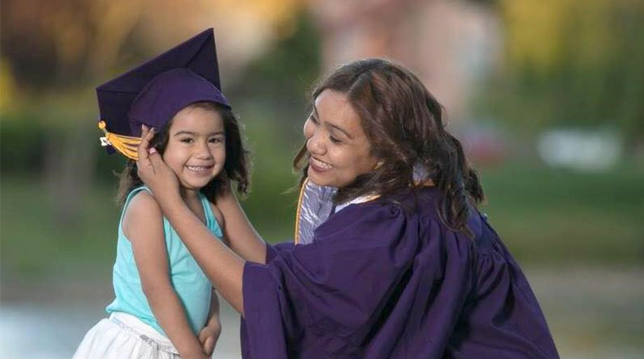 Graduate putting cap on young child