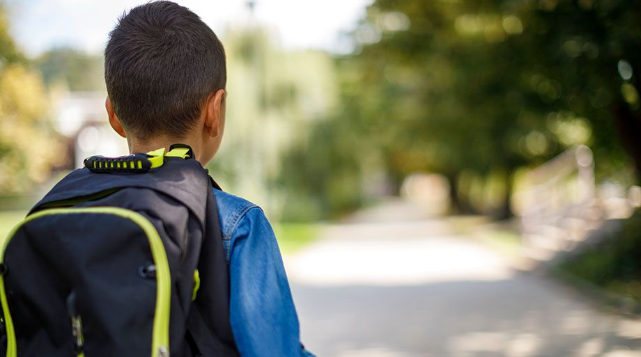Young boy wearing a backpack facing away from the camera