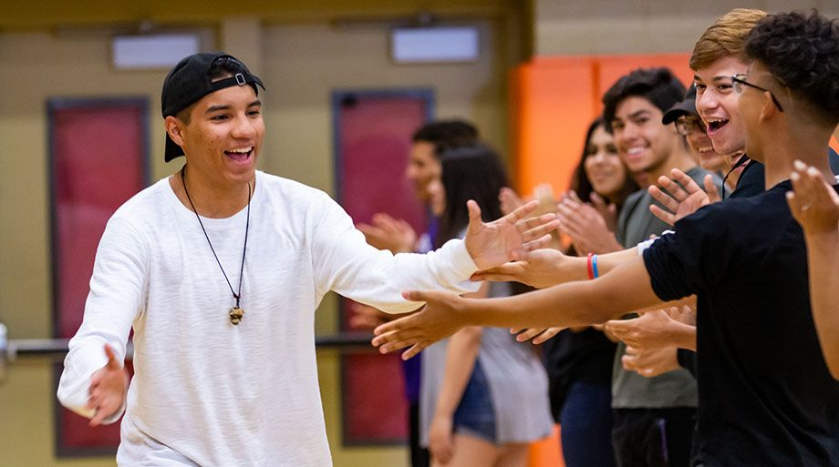 Young man giving high fives to high school age youth.