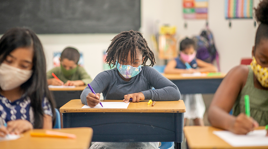 Student wearing mask working at desk